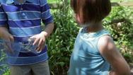 Stock Video Footage of Children Stop On A Trail, To Put Bug In A Jar, Then Continue Walking