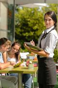 Waitress waiting for clients to decide order Stock Photos