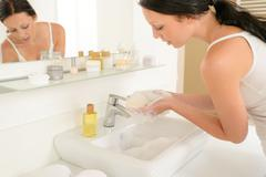 Woman bathroom hand-wash with soap above sink Stock Photos