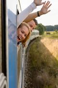 Couple screaming out train window waving happy - stock photo