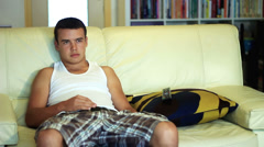 Adolescent, young boy, sitting on the sofa alone, television and mobile phones. Stock Footage