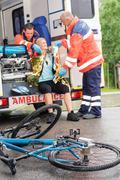Emergency ensihoitajat auttaa nainen pyörä onnettomuus Kuvituskuvat