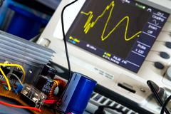 DC / DC converter and the switching waveform on the oscilloscope - stock photo