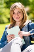 Teenage student sitting outside enjoying sunshine - stock photo