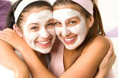 Blissful girls applying mask hugging each other - stock photo