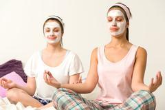 Meditating women wearing white facial mask Stock Photos
