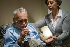 Senior man taking medication with water Stock Photos