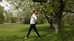 Girl doing stretching exercises in the spring garden Stock Footage