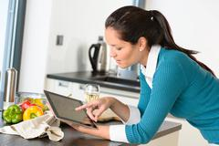 Young woman reading recipe tablet kitchen searching Stock Photos