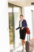 Smiling woman business flight attendant arriving home - stock photo