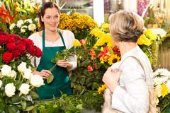 Young woman arranging flowers shop market selling Stock Photos