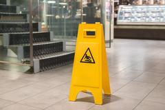 Yellow sign alerts for wet floor Stock Photos