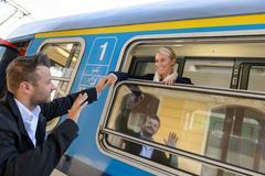 Man saying goodbye to woman on train Stock Photos