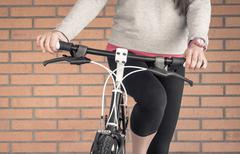 customized fixie bike and woman over brick wall - stock photo