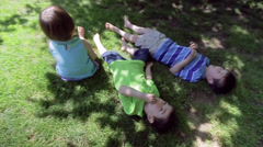 Stock Video Footage of Three Asian Children Relax In The Shade Of A Tree On A Hot Summer Day