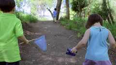 Two Little Kids Follow Their Older Brother Uphill In Beautiful Forest Setting Stock Footage