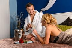 Lovers clinking champagne glasses bed enjoy anniversary - stock photo