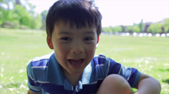 Little Asian Boy Sitting In A Field, Looks At The Camera And Makes Funny Faces Stock Footage