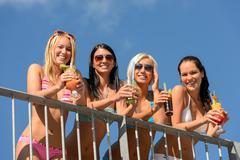 Beautiful women in bikinis smiling with drinks Stock Photos