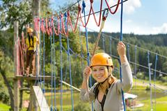 Woman climbing on rope ladder adrenalin park Stock Photos