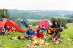 Camping students listening girl with guitar tents Stock Photos