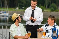 Smiling waiter taking order from men customers Stock Photos