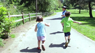 Stock Video Footage of Three Children Run Freely Down Park Path, Away from Camera