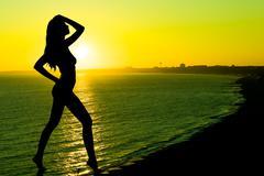 Sunset, sexy nude woman silhouette Stock Photos