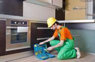 Repairman assembling the furniture at kitchen Stock Photos