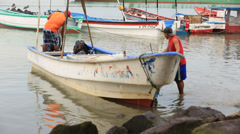 Fishermen in a small boat on shore Stock Footage