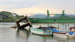 Oil tanker passes in background of small fishing boats and concrete debris Stock Footage