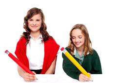 Cheerful girls writing with pencil on surface - stock photo