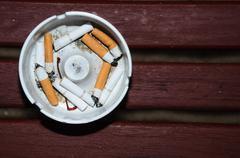 Smoked cigarettes in white ashtray on wood table Stock Photos