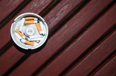 Smoked cigarettes in white ashtray on wood table Stock Photos