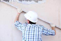 worker aligns wall - stock photo