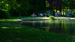 Munich English Garden visitors relax feed bird biking Germany Europe Stock Footage