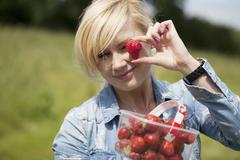 Woman holding up large ripe strawberry - stock photo