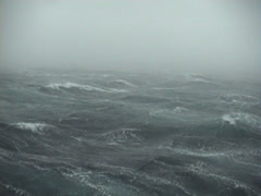 Ocean scenery pan across seas to skiffs during gale, storm, on very windy and Stock Footage