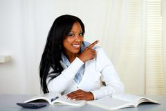 African student smiling and pointing to his left - stock photo