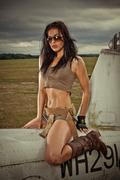Sexy woman astride aircraft fuselage Stock Photos