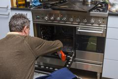 Man cleaning oven at home Stock Photos