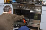 Stock Photo of man cleaning oven at home