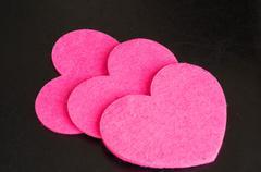 Three pink felt hearts against a dark background Stock Photos