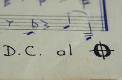 Da capo al fine in a music book with hand-written notes close up Stock Photos
