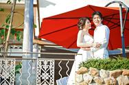 Stock Photo of portrait of romantic bride and groom with red umbrella