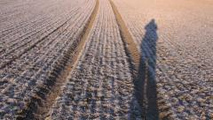 Frozen early spring  crop field and farmer shadow Stock Footage