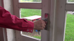 unlock with key and open farm house door in spring - stock footage