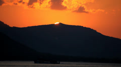 Sunset at sea, mountains in background and mooving ship. Zoom out - stock footage
