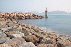 lighthouse on a rocky breakwall: a small lighthouse warns of a rough shorelin - stock photo