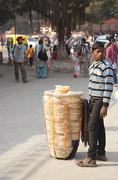 A boy trying to sell bread in the street of India - stock photo